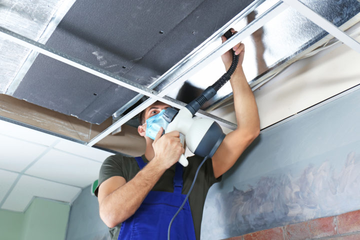 HVAC worker cleaning ducts