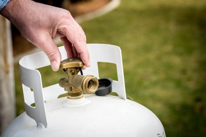 hand on valve of propane tank