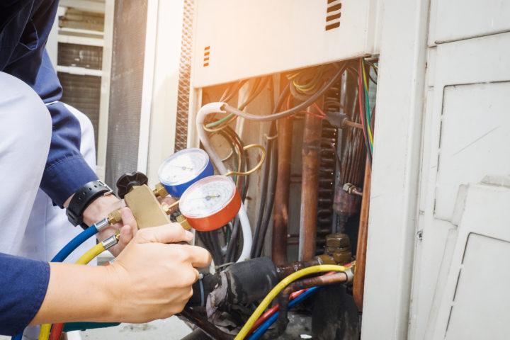 HVAC worker checking dials