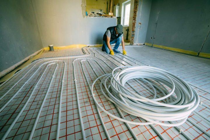 HVAC worker installing geothermal tubing in floor