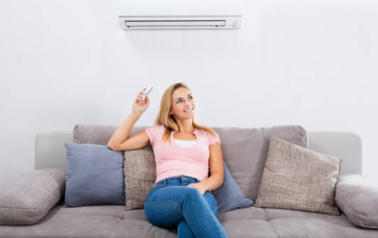 Woman sitting under ductless A/C unit