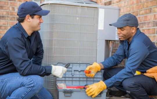 two hvac workers squatting near air conditioner